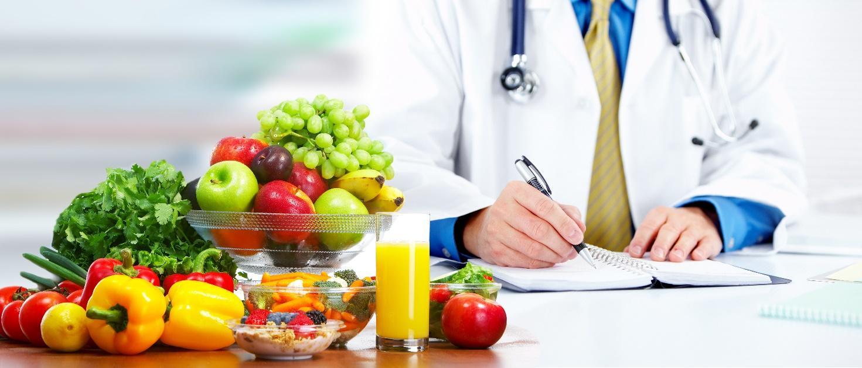 Lekarz piszący coś wzeszycie, nastole leży zdrowa żywność.